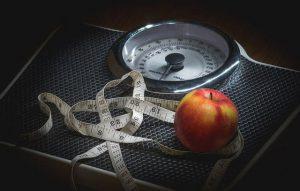 miarka i jabłko leżące na wadze pokojowej