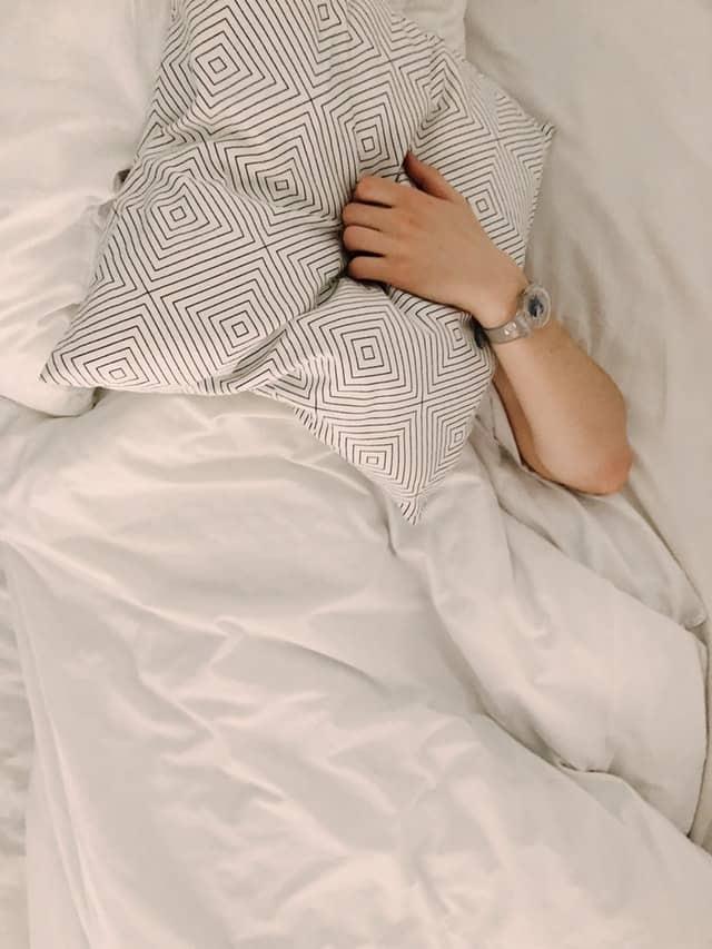 człowiek nakryty poduszką