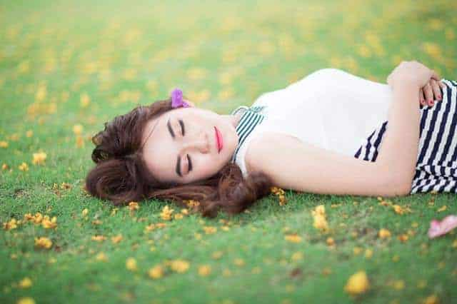 kobieta śpiąca na trawie