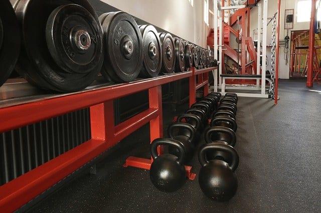 ciężary ułożone na półce i hantle na podłodze siłowni