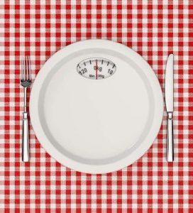 talerz z podziałką wagi i sztućce na stole