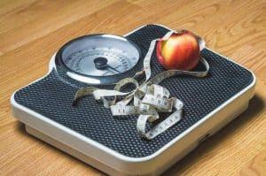 jabłko i miarka leżące na wadze