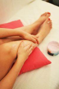 kobieta smaruje nogi kremem