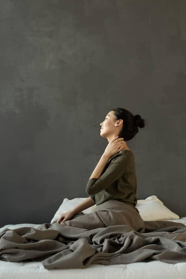kobieta siedząca na łóżku i trzymająca się za szyję, ból pleców