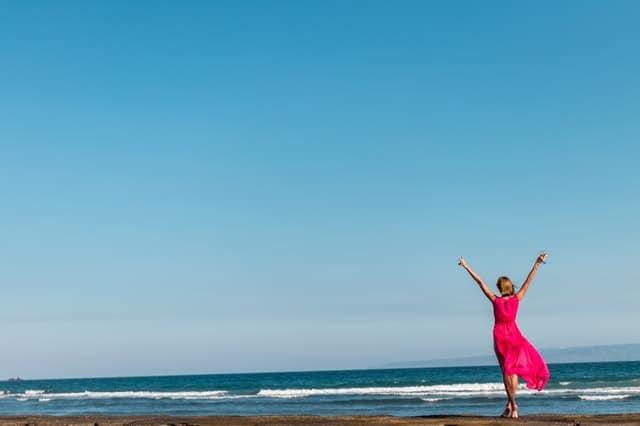kobieta w czerwonej sukience stojąca na wybrzeżu