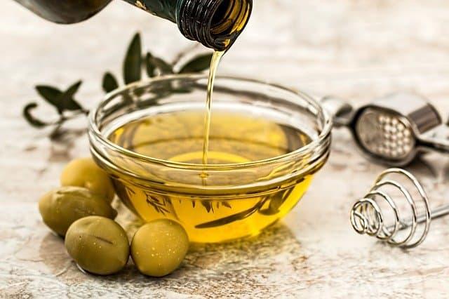 oliwa nalewana do miseczki, obok zielone oliwki