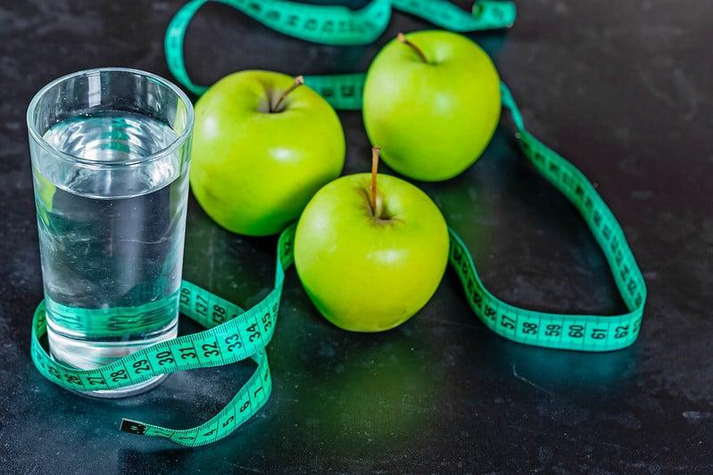 szklanka wody, zielone jabłka i centymetr krawiecki