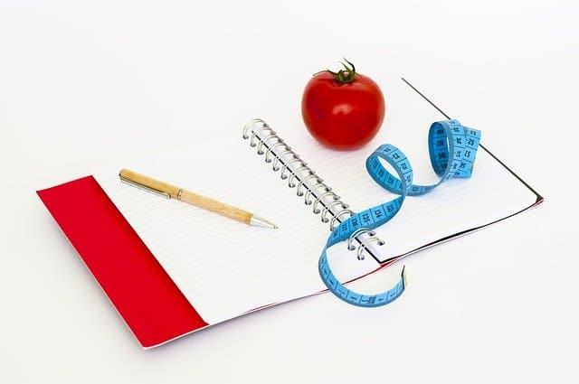 notes, długopis, miarka krawiecka i pomidor