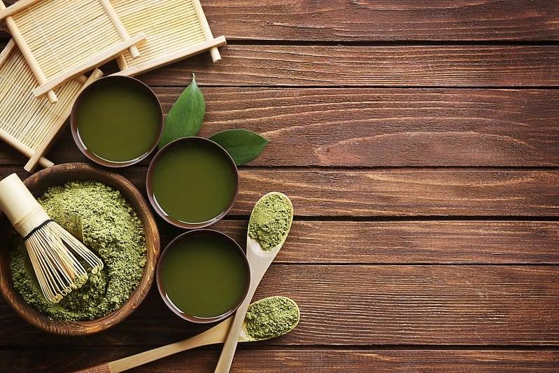 zielona herbata matcha w proszku w salaterce i w filiżankach w formie płynnej