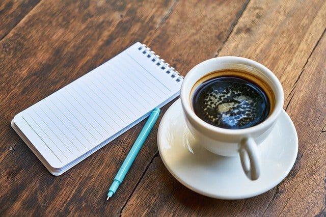 filiżanka z kawą, notatnik, długopis