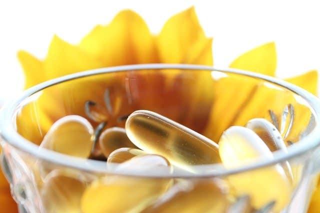 tabletki w szklance, żółty kwiat w tle