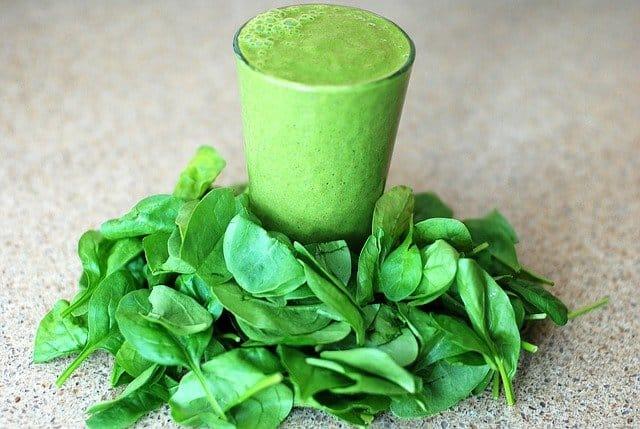 szklanka z zielonym koktajlem, dookoła liście szpinaku
