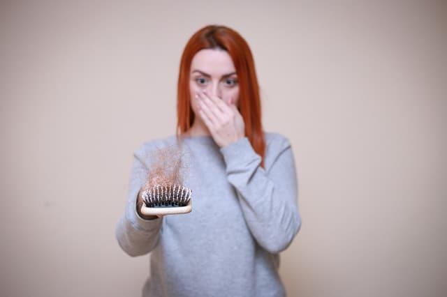 kobieta patrzy na szczotkę do włosów pełną włosów