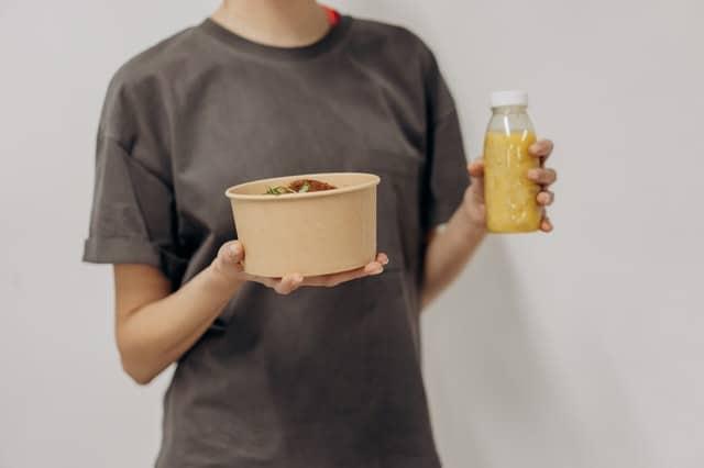 kobieta trzyma miseczkę z jedzeniem i koktajl
