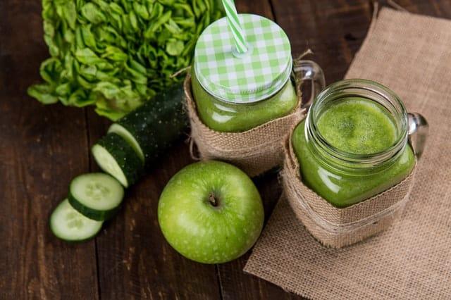 zielone smoothie w szklankach, obok zielone warzywa i owoce