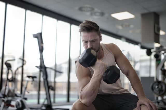 mężczyzna trenuje z hantlami w siłowni