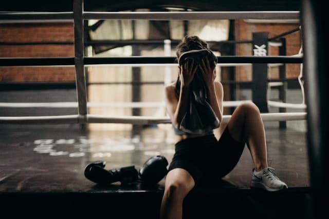 kobieta wyciera pot z twarzy po wyczerpującym treningu