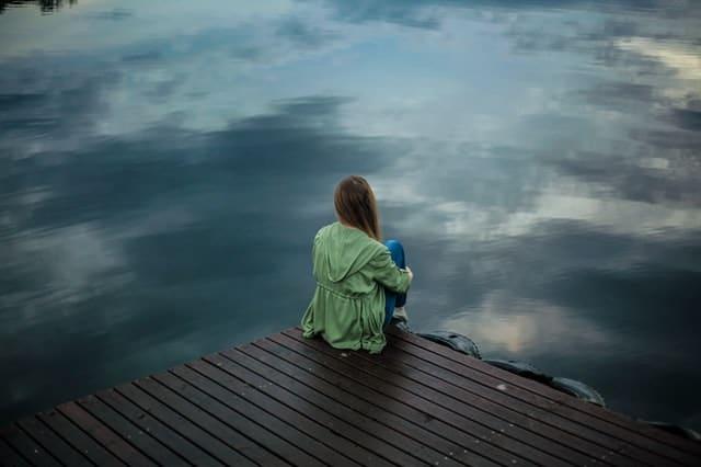 kobieta siedzi na skraju molo i patrzy w wodę