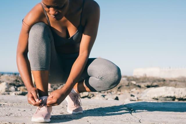 kobieta w stroju sportowym zawiązuje but